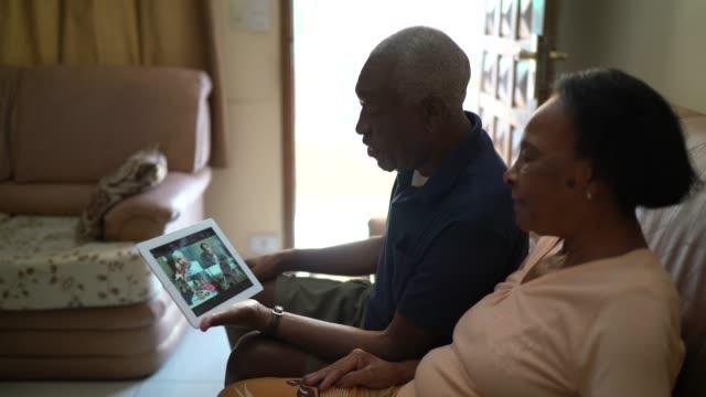 Couples aînés sur une appel vidéo utilisant une tablette numérique à la maison