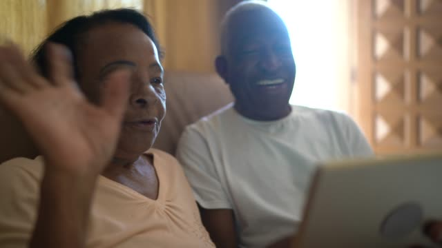 senior couple on a video calling using a digital tablet at home - senior adult stock videos & royalty-free footage