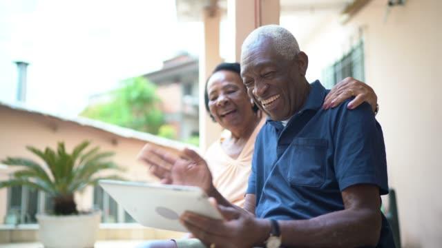 vídeos de stock, filmes e b-roll de casal de idosos em um vídeo chamando usando tablet digital em casa - homens idosos