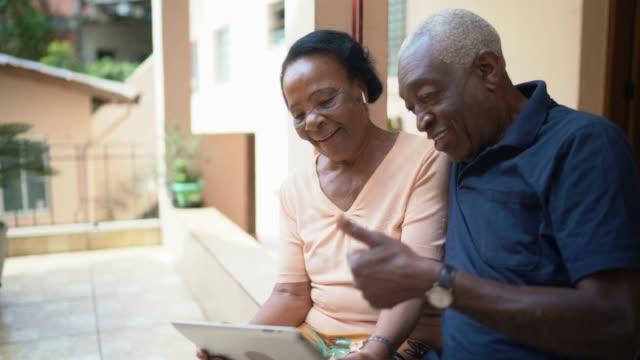 vidéos et rushes de couples aînés sur une appel vidéo utilisant la tablette numérique à la maison - webinaire