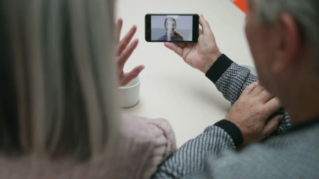 senior couple on a videocall to daughter - över axel perspektiv bildbanksvideor och videomaterial från bakom kulisserna