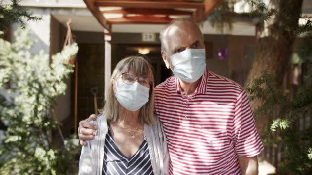 coppia senior davanti alla loro casa durante la quarantena covid-19 - affettuoso video stock e b–roll