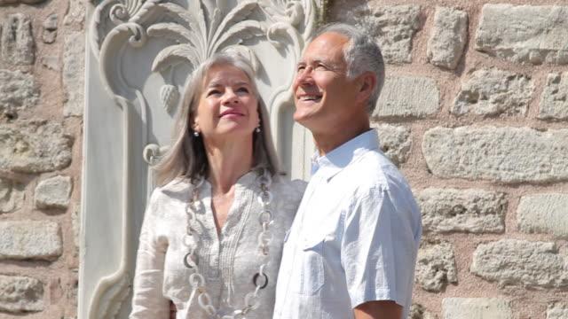 stockvideo's en b-roll-footage met senior couple on holiday walking and looking around - jong van hart
