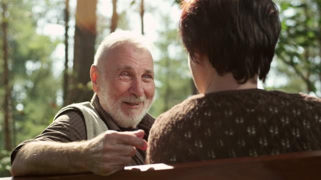 coppia senior sulla panchina pubblica - uomini anziani video stock e b–roll