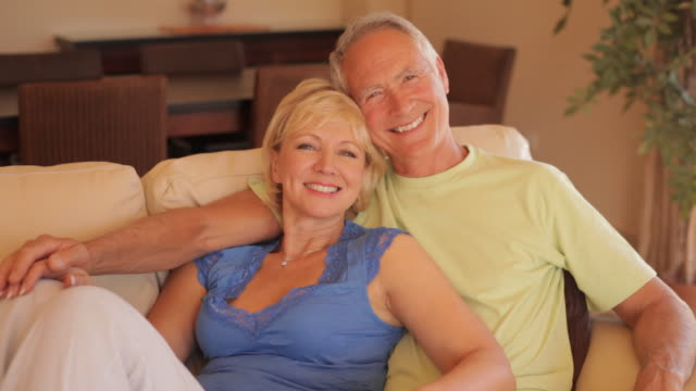 senior couple on sofa watching tv