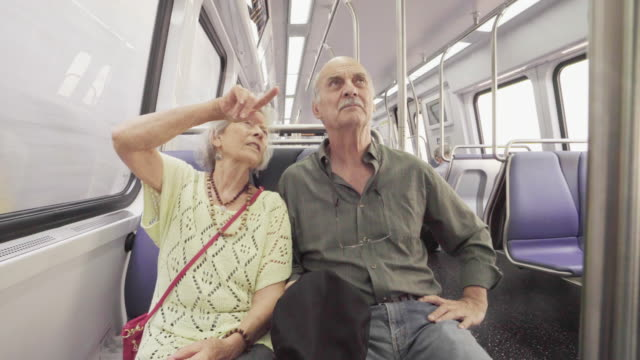 vídeos de stock e filmes b-roll de senior couple on subway train - transporte público