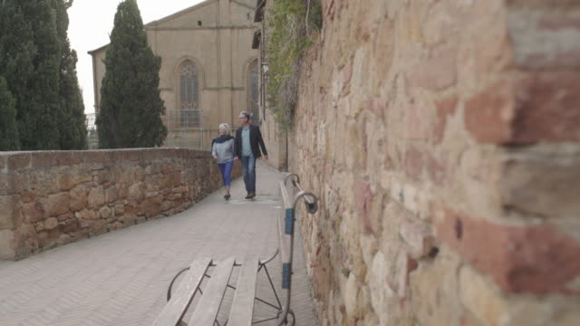 Senior couple on vacation walking in village