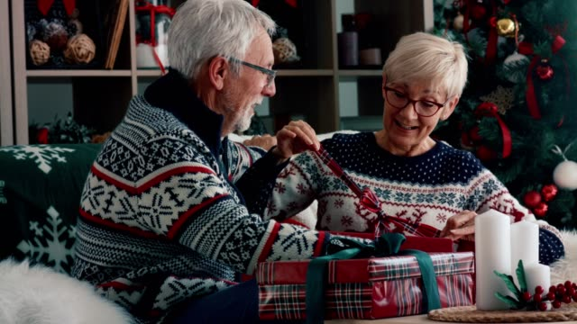 senior couple opening christmas gifts - gift box stock videos & royalty-free footage