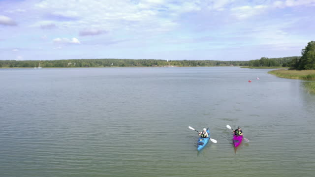 senior couple out kayaking on a summer day - using a paddle stock videos & royalty-free footage