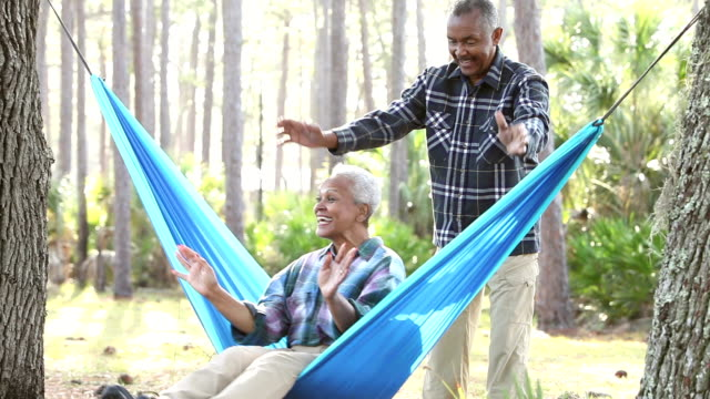 senior couple outdoors, swinging on hammock - swinging stock videos & royalty-free footage