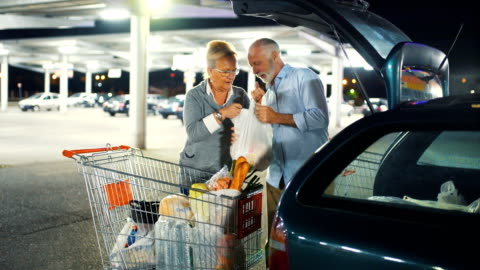 senior couple packing groceries after shopping. - plastic bag stock videos & royalty-free footage