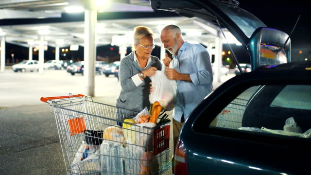 senior couple packing groceries after shopping. - bag stock videos & royalty-free footage