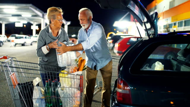 senior couple packing groceries after shopping. - car park stock videos & royalty-free footage