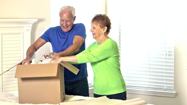 Senior couple packing personal belongings