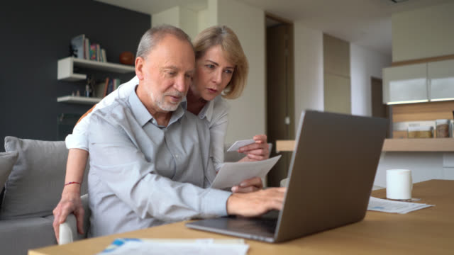 senior couple paying bills at home using a credit card and a laptop both smiling - online shopping stock videos & royalty-free footage