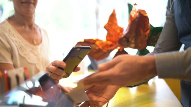 vídeos de stock, filmes e b-roll de casal de idosos pagando pelo celular em uma loja - comprando ovos de páscoa - sales occupation