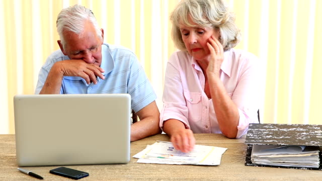 stockvideo's en b-roll-footage met senior couple paying their bills with laptop - oudere internetgebruiker