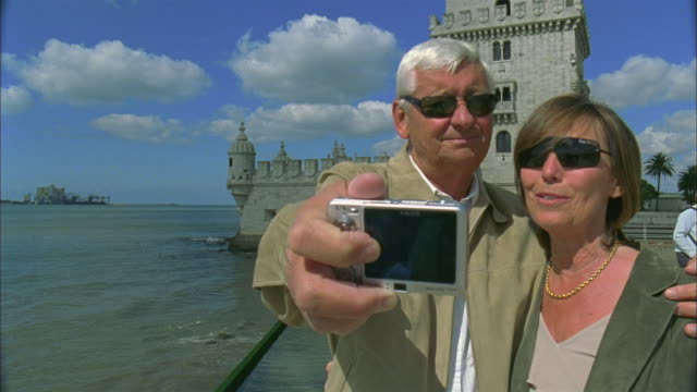 vídeos y material grabado en eventos de stock de cu, senior couple photographing self in front of belem tower, lisbon, portugal - monumento