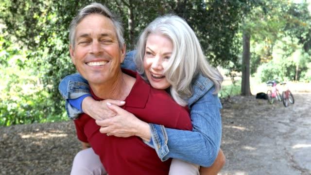 vidéos et rushes de senior couple piggyback ride dans la nature - soulever