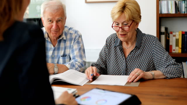 senior couple planning their investments with financial advisor - financial advisor stock videos & royalty-free footage