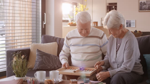 ds senior couple playing a board game on the sofa - board game stock videos & royalty-free footage