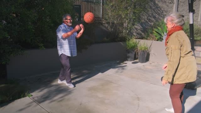 vídeos y material grabado en eventos de stock de pareja mayor jugando baloncesto en el patio - encestar