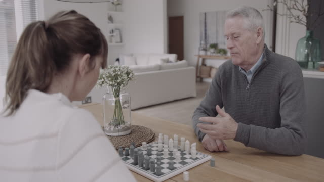 senior couple playing chess at home at table, day in life - male likeness stock videos & royalty-free footage