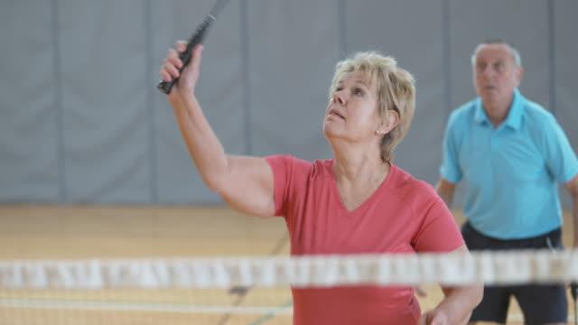vídeos de stock, filmes e b-roll de casal sênior jogando duplas badminton indoor - badmínton esporte