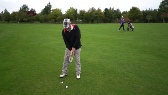 a senior couple playing golf. - sun visor stock videos and b-roll footage
