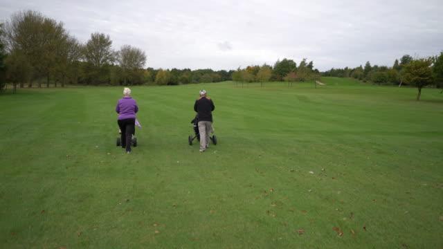 vídeos de stock, filmes e b-roll de a senior couple playing golf. walking away from camera on the fairway. - bolsa de golfe