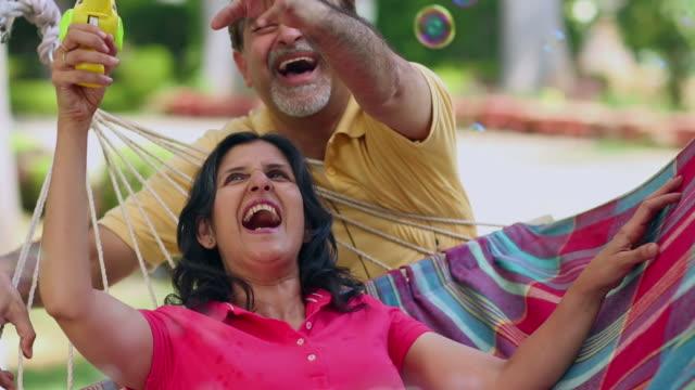 Senior couple playing with bubble wand, Delhi, India