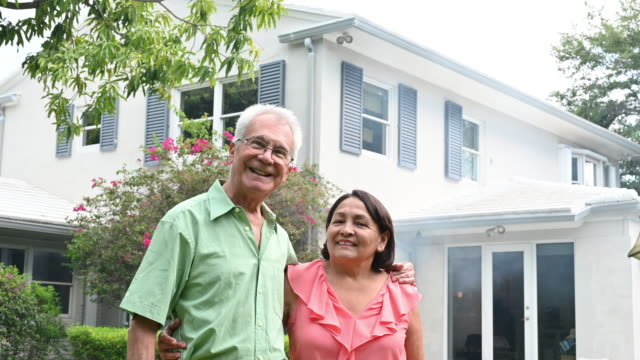 Senior couple portrait outside their detached house