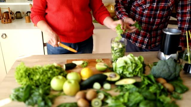 vídeos y material grabado en eventos de stock de senior pareja preparando los ingredientes para el licuado verde - antioxidante