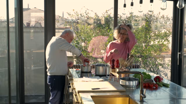senior couple preparing lunch in sunny kitchen - pull out camera movement stock videos & royalty-free footage