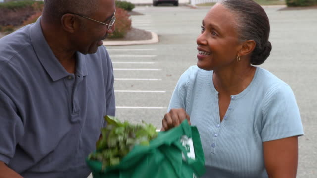 CU TU Senior Couple pushing shopping cart in parking lot and putting groceries into car with reusable bags/ Richmond, Virginia