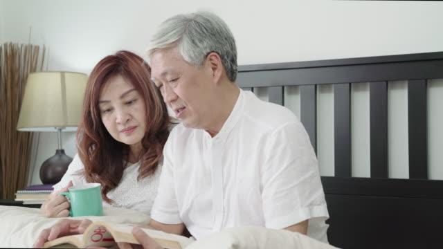4k uhd :シニアカップルは、自宅の寝室でベッドの上で本を読みます。 - くつろぐ点の映像素材/bロール