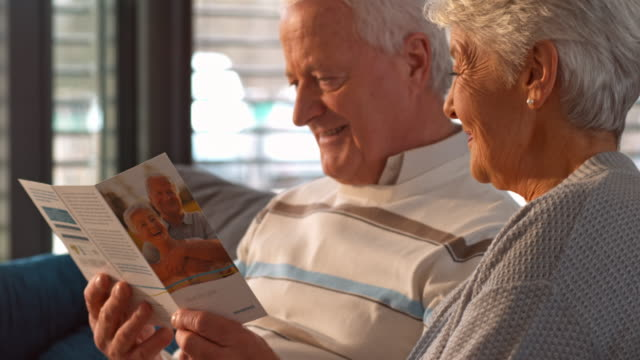 senior couple reading a leaflet on the sofa in the morning - brochure stock videos and b-roll footage