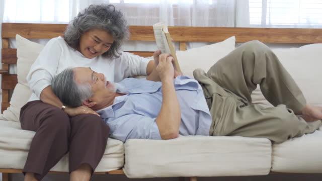 vidéos et rushes de livre de lecture de couples aîné ensemble - propriétaire immobilier