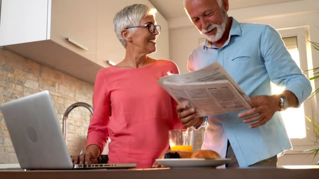 Senior couple reading news during breakfast in a sunny kitchen
