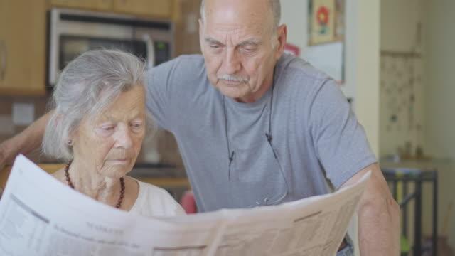 senior-paar liest gemeinsam die zeitung - reportage stock-videos und b-roll-filmmaterial
