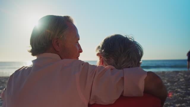 älteres paar entspannend am strand im sommer - sitting stock-videos und b-roll-filmmaterial