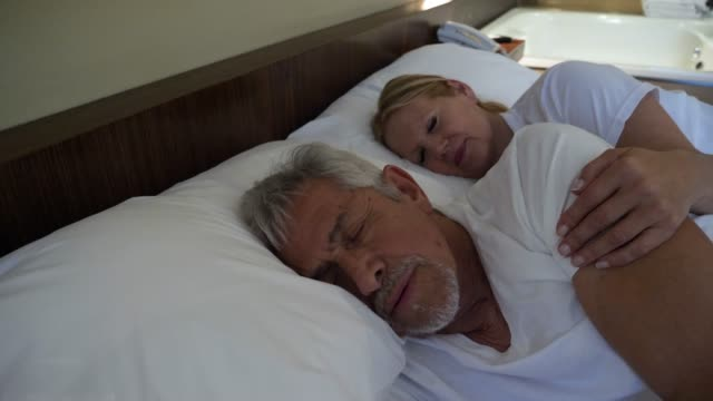 Senior couple relaxing at their hotel room sleeping very profoundly and woman putting her arms on her partners shoulder