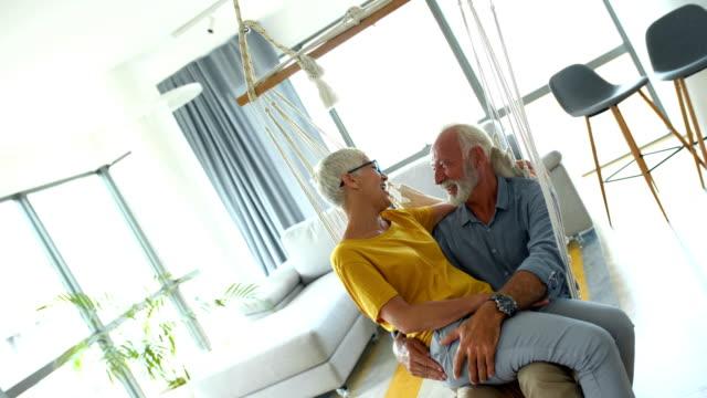 stockvideo's en b-roll-footage met senior paar ontspannen in een schommel schommel - schommelen schommelstoel