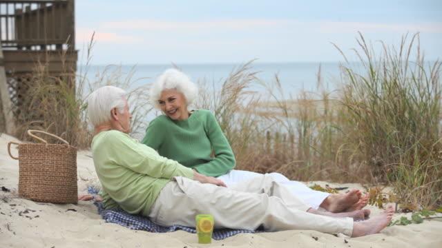 ws senior couple relaxing on beach, eastville, virginia, usa - eastville stock videos and b-roll footage