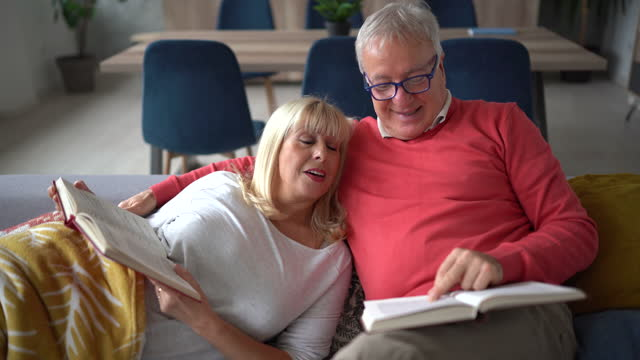 senior couple relaxing on sofa and reading book at home - senior couple stock videos & royalty-free footage
