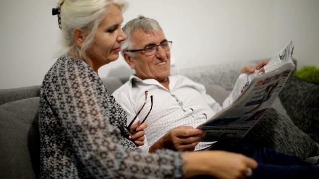 Senior paar ontspannen op de Sofa thuis lezing krant