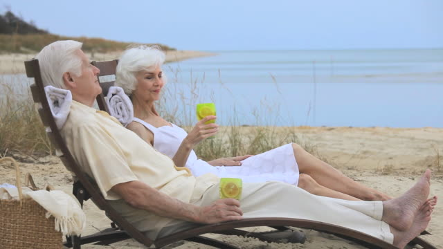 ms pan senior couple relaxing together on beach, toasting with drinks, eastville, virginia, usa - outdoor chair stock videos & royalty-free footage