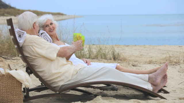 ms pan r/f senior couple relaxing together on beach, toasting with drinks, eastville, virginia, usa - eastville stock videos and b-roll footage