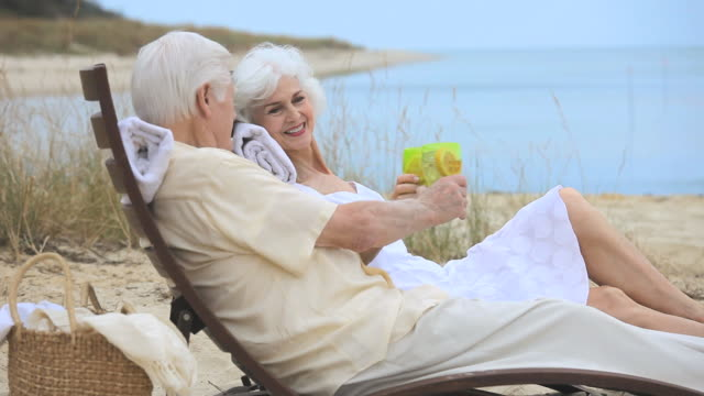 ms senior couple relaxing together on beach, toasting with drinks, eastville, virginia, usa - eastville stock videos and b-roll footage