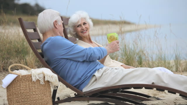 MS Senior couple relaxing together on beach, toasting with drinks, Eastville, Virginia, USA